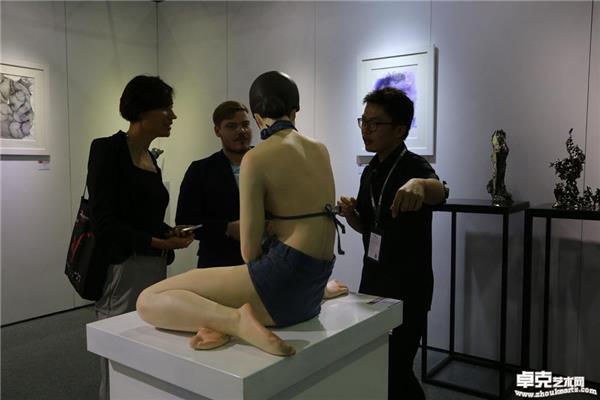 外国艺术家在展览现场就作品《背影》与工作人员交流